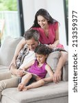 family sitting on a couch... | Shutterstock . vector #213359377