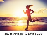 woman running on the beach at... | Shutterstock . vector #213456223
