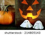 Small photo of Scary Halloween party background with a glowing paper bag jack-o-lantern with a fiendish face alongside a fresh pumpkin and cute scary little ghosts made of pastry dough for a creative snack