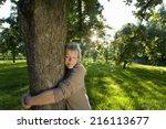 Mature Woman Embracing Tree ...