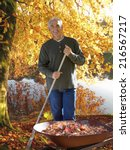 Stock photo man raking autumn leaves at edge of lake 216567217