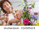 Smiling Woman Trimming Flowers...