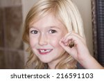 child holding her missing front ... | Shutterstock . vector #216591103