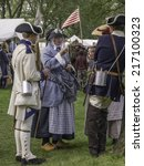 Small photo of WHEATON, ILLINOIS/USA - SEPTEMBER 13, 2014: An unidentified woman in period dress socializes with compatriot actors in a military camp at a reenactment of the American Revolutionary War (1775-1783).