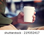 Small photo of Young woman drinking coffee from disposable cup