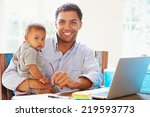 Father With Baby Working In...