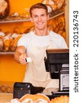 Small photo of Here is your card! Handsome male cashier stretching out plastic card and smiling while standing in bakery shop
