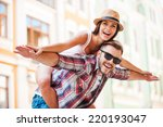 Stock photo happy loving couple happy young man piggybacking his girlfriend while keeping arms outstretched 220193047