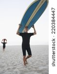 Senior Surfers Carrying Their...
