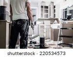 Small photo of Mess of All kind of Painting Equipment in the Kitchen and Discouraged Man