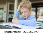Small photo of concentrated little boy doing homework