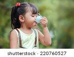 little asian girl drinking...   Shutterstock . vector #220760527