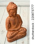 Small photo of Buddha stature sitting on old wood