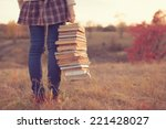 hipster girl holding a stack of ... | Shutterstock . vector #221428027
