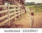 little boy feeding a giraffe at ... | Shutterstock . vector #223150417