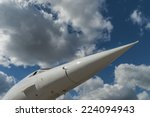 Pointed nose cone and windscreen of the supersonic aircraft Concorde against a blue sky with white clouds, shot from beneath