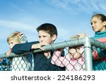 Children Standing Behind Fence