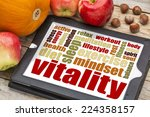 Small photo of vitality or vital energy word cloud on a digital tablet with apples, pumpkin and hazelnuts
