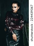 Small photo of beautiful woman in claret shirt and leather skirt