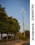Small photo of aerogenerator and trees with blue autumn sky