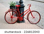 A Bicycle Is Red With The Smal...