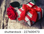 rose and present gift on wooden