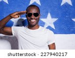 Small photo of Yes sir yes! Happy young African man in sunglasses holding hand near forehead and smiling while standing against American flag