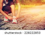young woman runner tying... | Shutterstock . vector #228222853