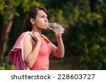 a girl drinks water after sport | Shutterstock . vector #228603727