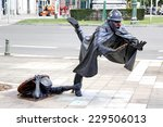 Small photo of BRUSSELS, BELGIUM - AUGUST 9, 2014: Statue De Vaartkapoen of a toppling policeman illustrating a cartoon serial about Quick and Flupke.