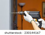 hands holding electric drill in ... | Shutterstock . vector #230144167