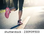 Sporty Woman Running On Road A...