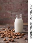 Small photo of Almond milk in a glass jar with almonds rustic background vertical