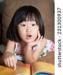 Small photo of Asian little girl read her book aloud.Shallow DOF