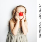 Small photo of a little girl wearing a clown nose