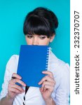 Small photo of Young beautiful woman holding a address book