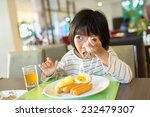 asian girl eating breakfast  | Shutterstock . vector #232479307