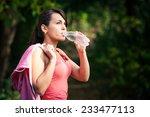 a girl drinks water after sport | Shutterstock . vector #233477113