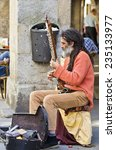 Small photo of SANTIAGO DE COMPOSTELA, SPAIN - JULY 14, 2014: A man with white slime and hindu garb, plays the sitar in one of the streets of the historic town.