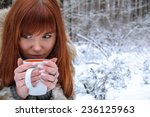 Small photo of Portrait of the girl close-up with a cup of drink squirm in the winter forest