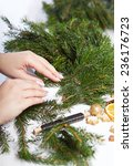 Small photo of Woman affixing branches spruce needles on Christmas wreath