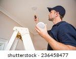 handyman installing smoke... | Shutterstock . vector #236458477