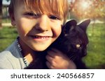 Stock photo child shows with affection his black cat 240566857