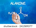 Small photo of Hand with pen drawing the chemical formula of alanine