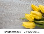 Yellow Tulips On A Wooden...