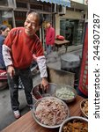 Small photo of Shanghai, China - April 20, 2010: Outdoor affable chef prepares dishes trades in a narrow street.