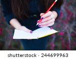 Small photo of girl on nature writing in a notebook