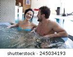 couple relaxing in jacuzzi of... | Shutterstock . vector #245034193