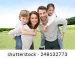 young parents giving piggyback... | Shutterstock . vector #248132773