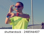 Small photo of Urban jogger on a big bridge checking his running time.